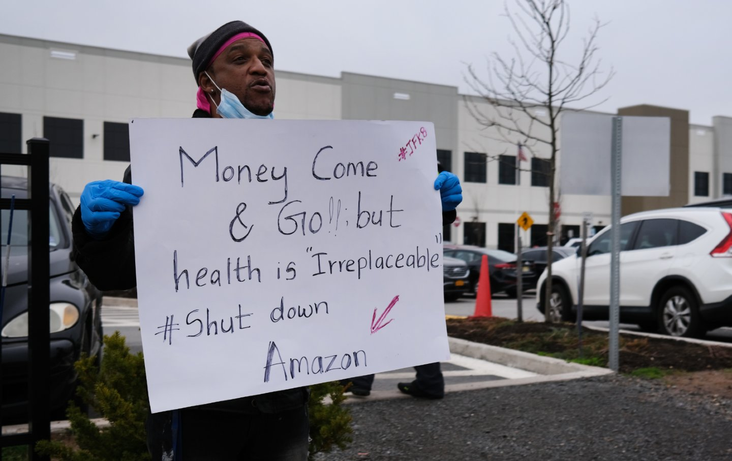 A worker stands outside an Amazon warehouse holding a sign that says
