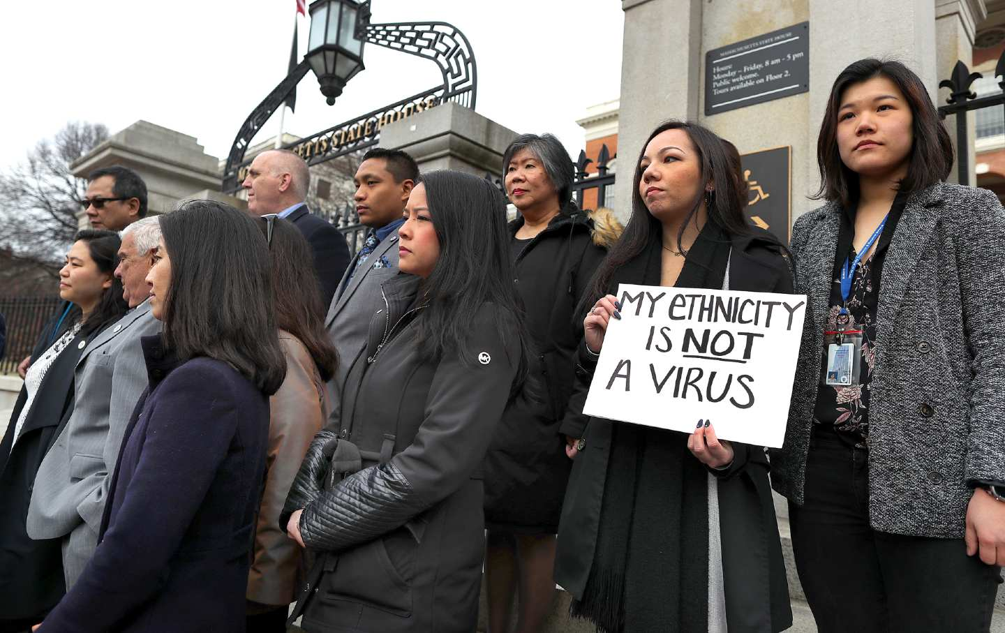 Asian Americans stand together on the steps of a building, one holds a sign reading