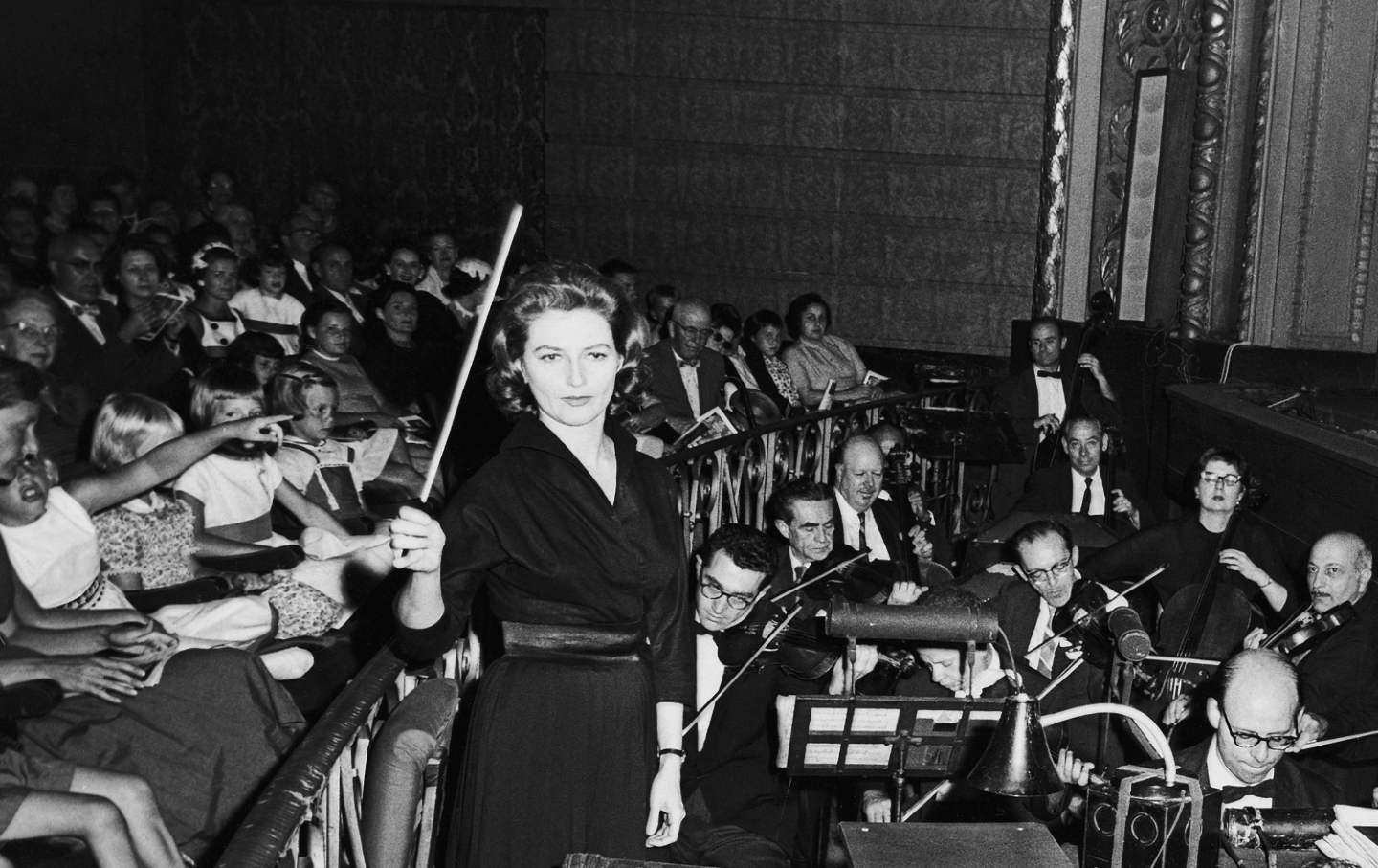 A conductor raises her baton in an orchestra pit, surrounded by musicians