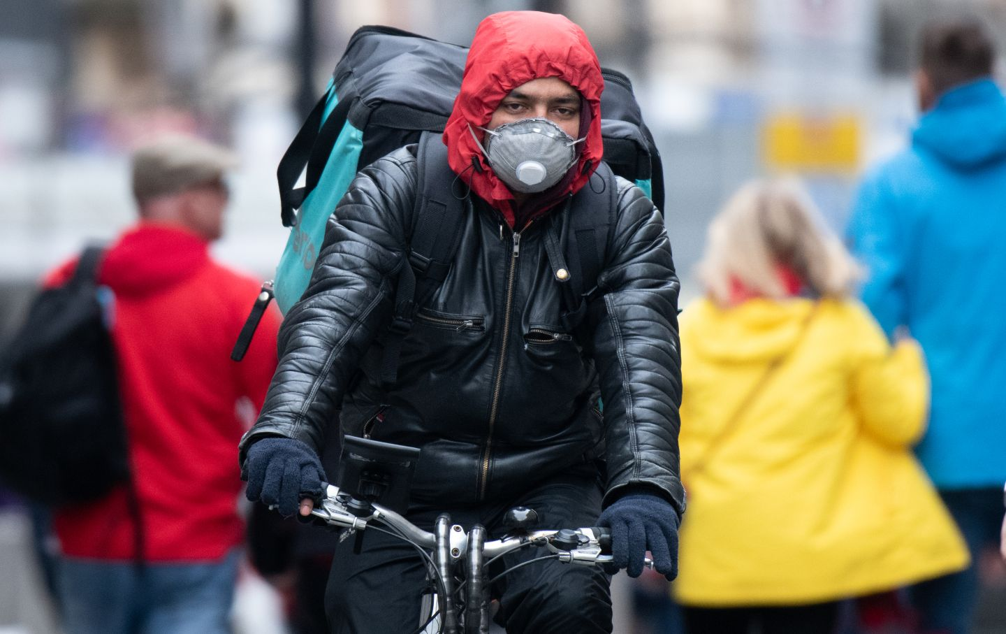 Food service worker biking with a mask
