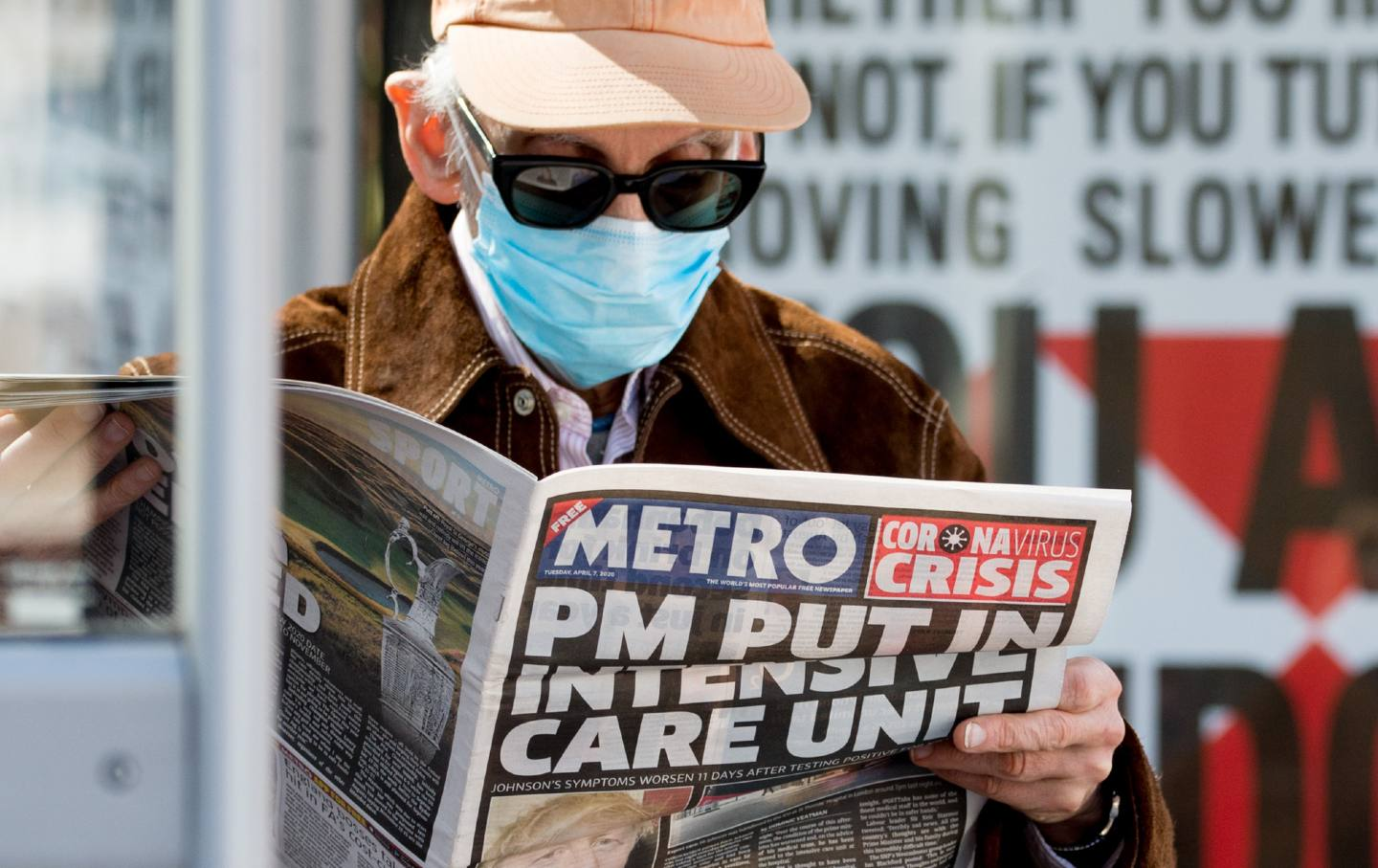 A man wearing a surgical mask reads the Metro newspaper