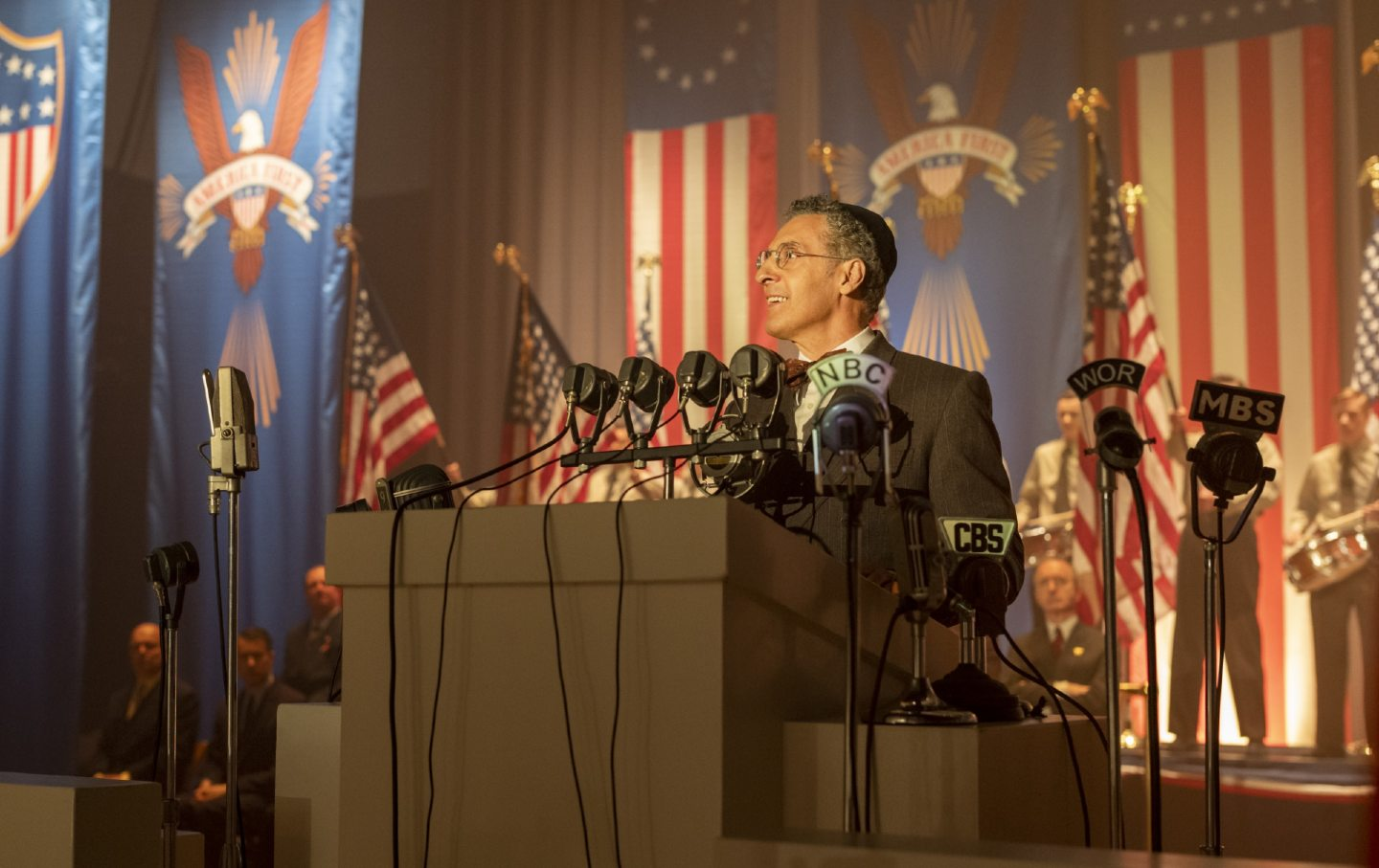 John Turturro stands at a podium with microphones, playing a rabbi in The Plot Against America