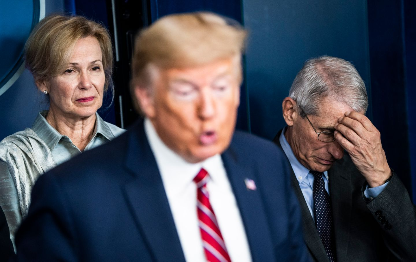 Donald Trump speaks while Dr. Anthony Fauci holds his head and looks down an Dr. Deborah Birx looks displeased