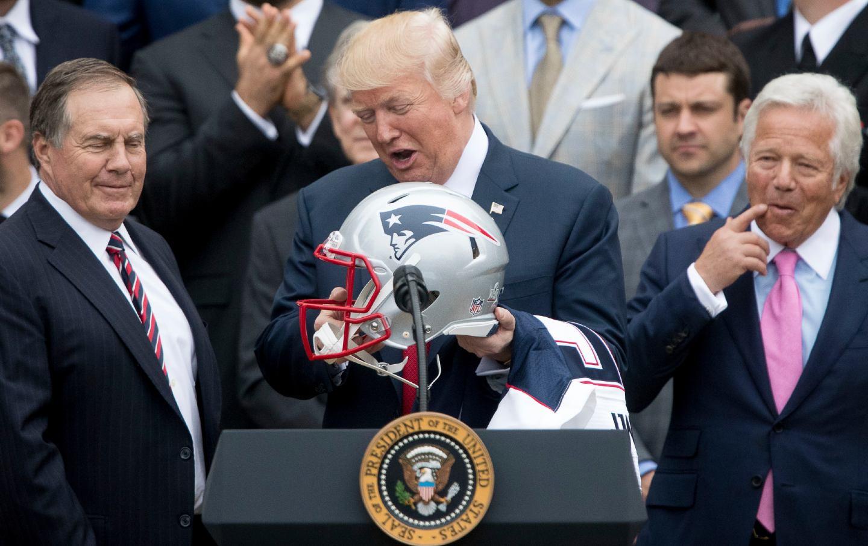 Trump holding a Patriots helmet