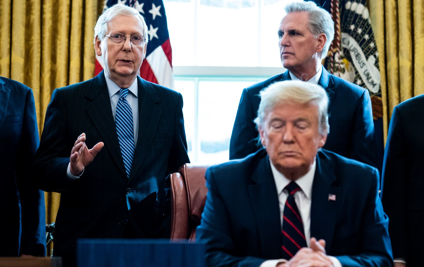 Donald Trump sits at a desk with Mitch McConnell and Kevin McCarthy standing behind him