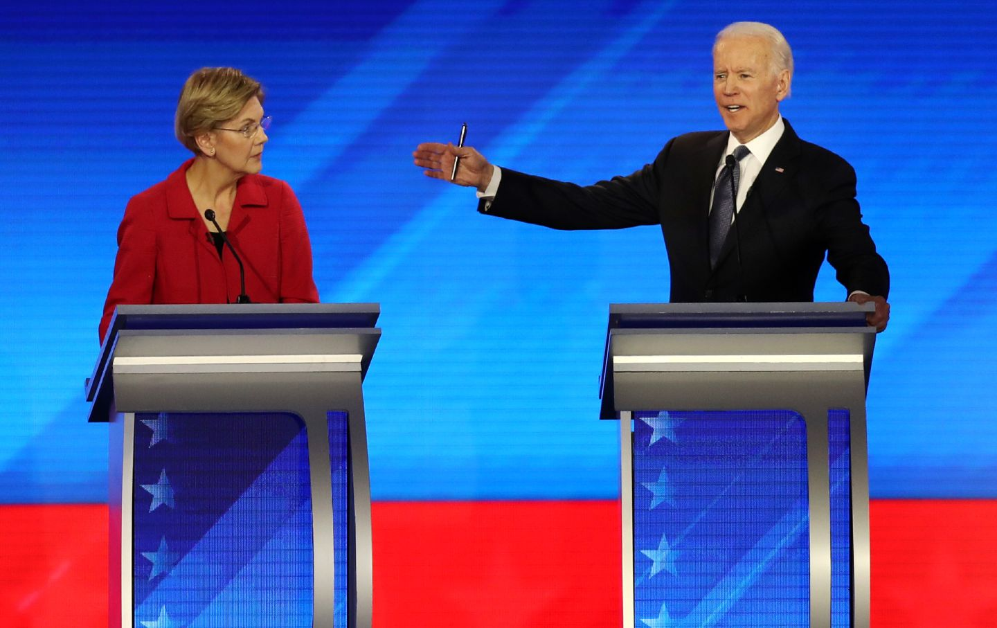 Elizabeth Warren and Joe Biden stand at their podiums at the presidential debate. Biden's hand is up, gesturing toward Warren.