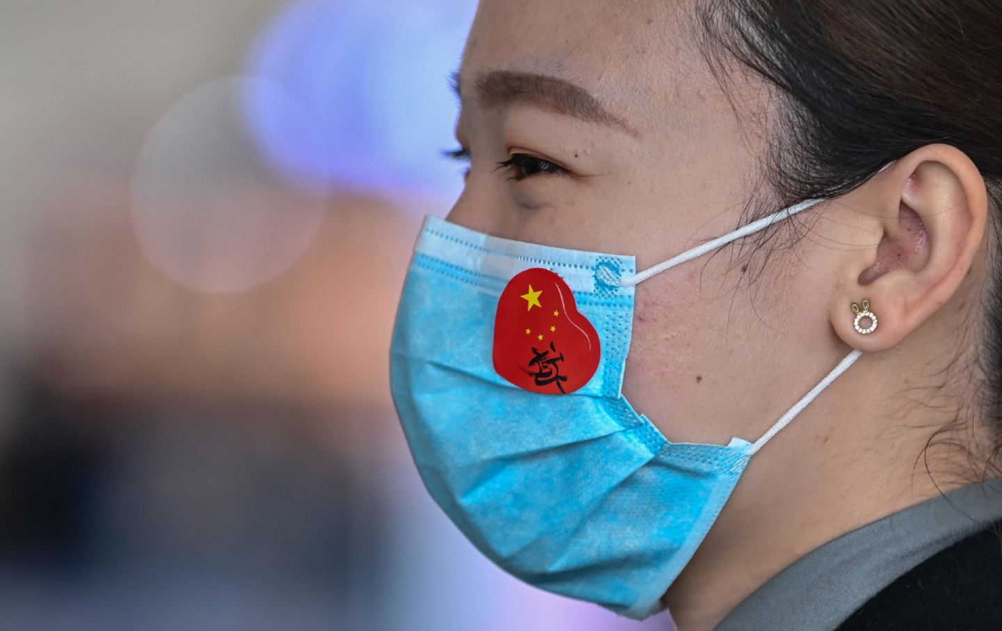 An airport worker wears a face mask with a sticker of the Chinese flag