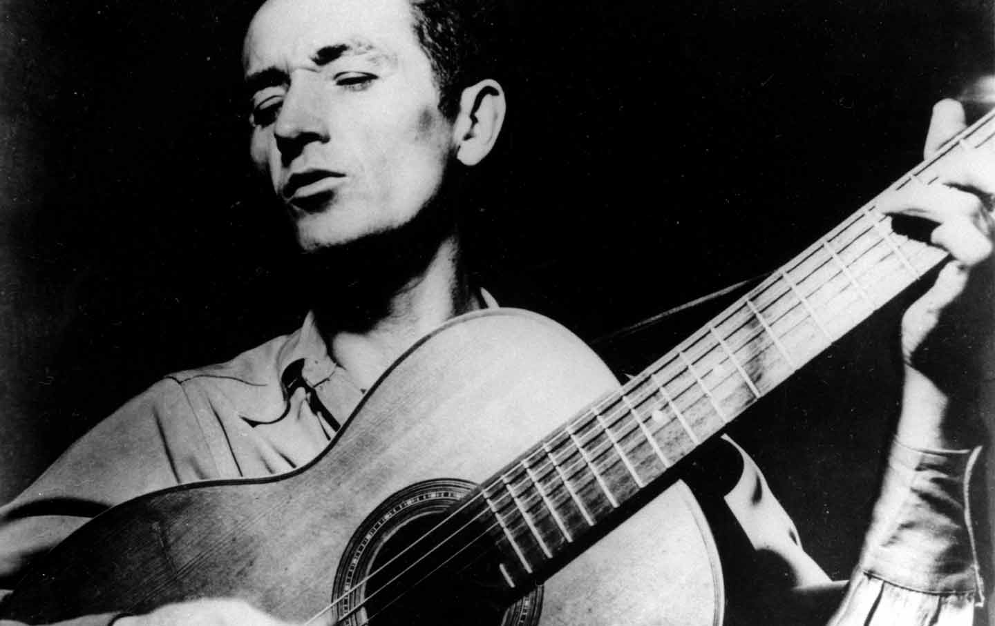 woody-guthrie-guitar-playing-ap-img