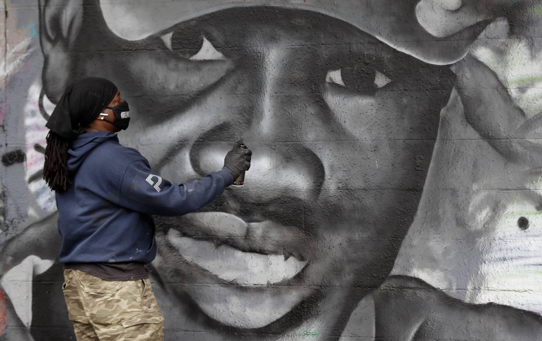 Artist creating a mural of Ahmaud Arbery