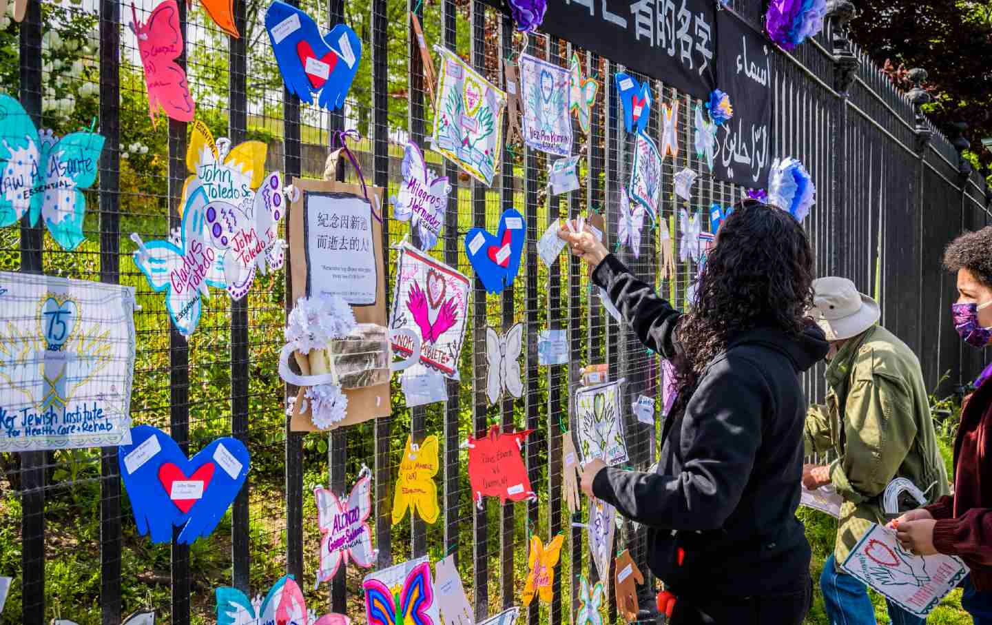 People hang signs on a fence commemorating those lost to Covid-19