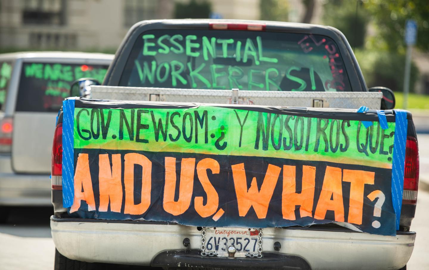 A car drives past city hall, carrying signs that read