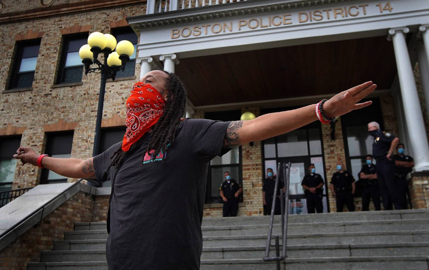 A Black Lives Matter protester wears a bandanna as a mask while speaking at a protest