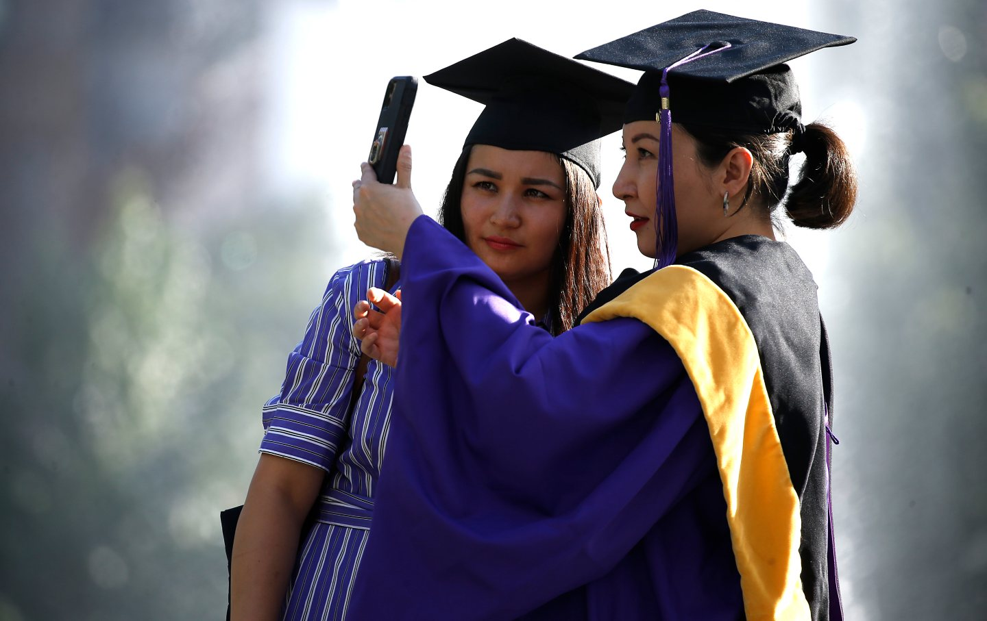 Two people pose for graduation photos