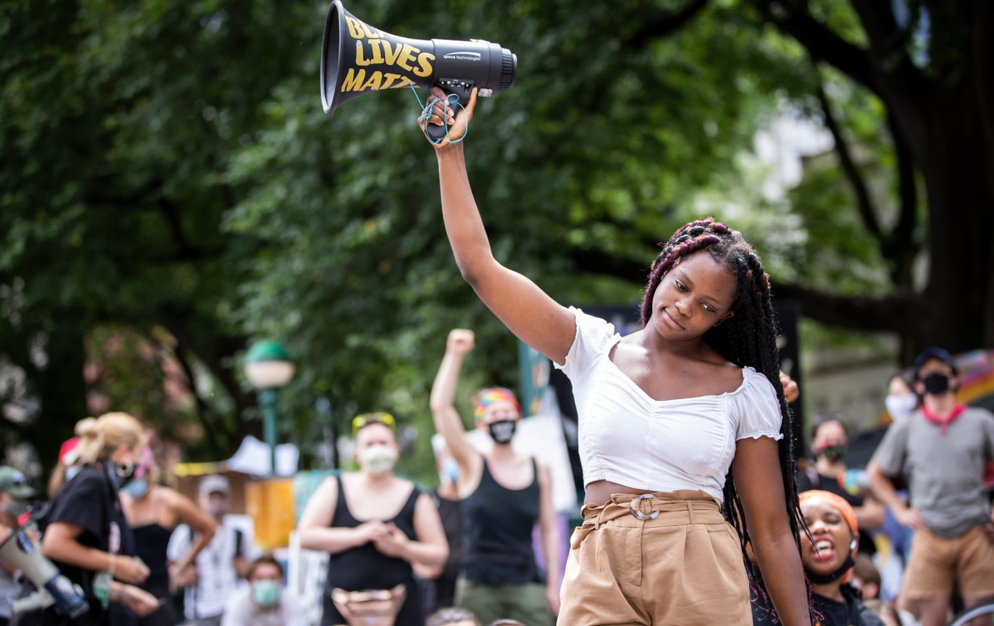 Kiara Williams holds a megaphone in the air that says
