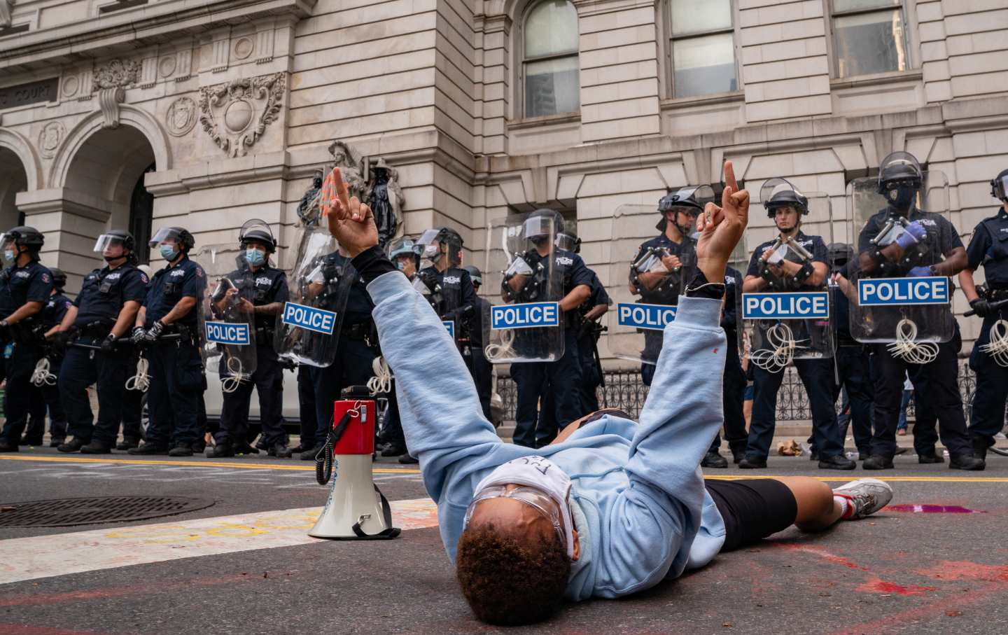A person lies on the ground in front of a group of police officers
