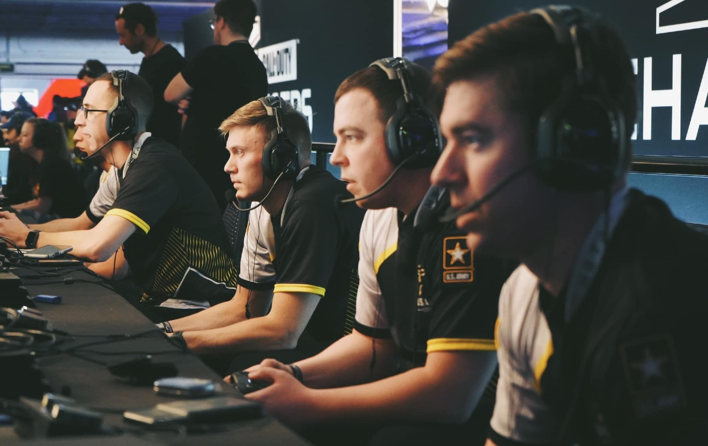 Five people with headsets look off stage at screens