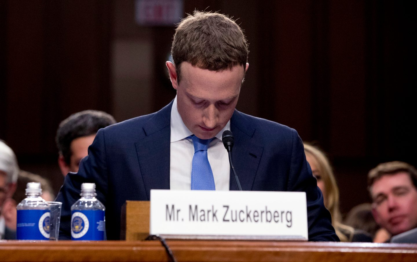 Mark Zuckerberg stares down at his lap