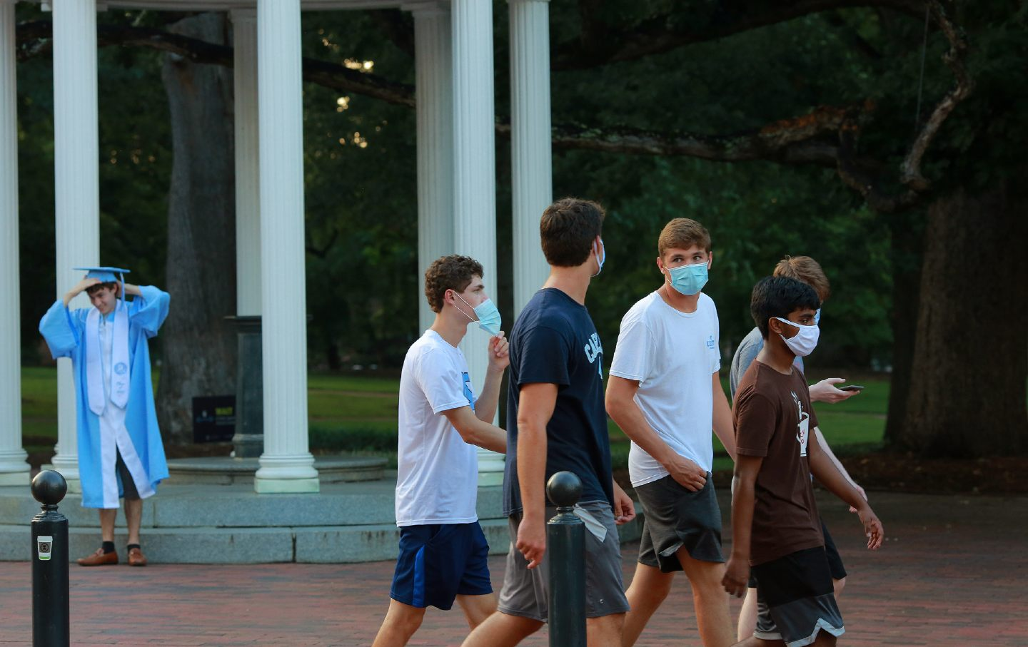 A group of five UNC freshman boys walk on campus wearing masks.