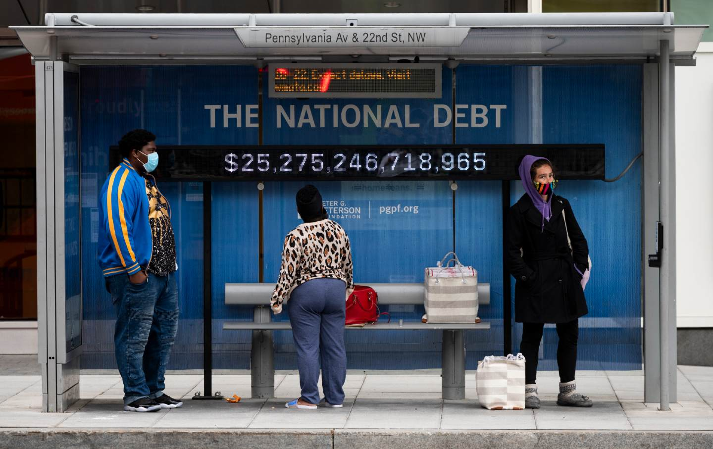 Passengers wearing face masks wait for their bus in front of a national debt display
