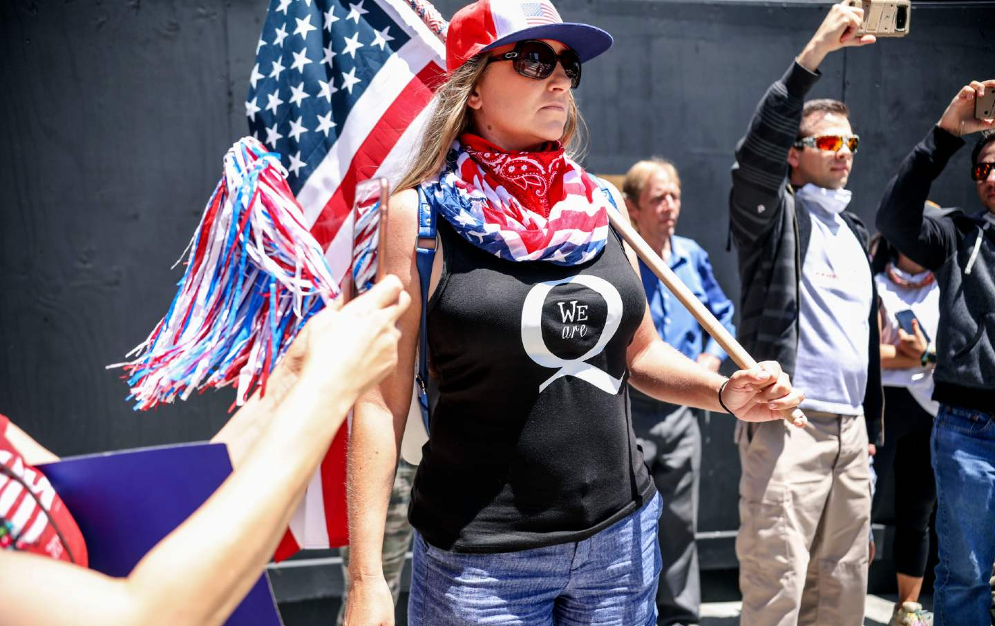A woman in a shirt showing support for the QAnon conspiracy theory holds an American flag.