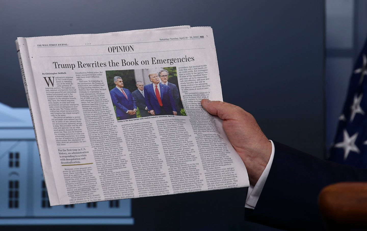 Donald Trump holds up WSJ Opinion section with an editorial titled