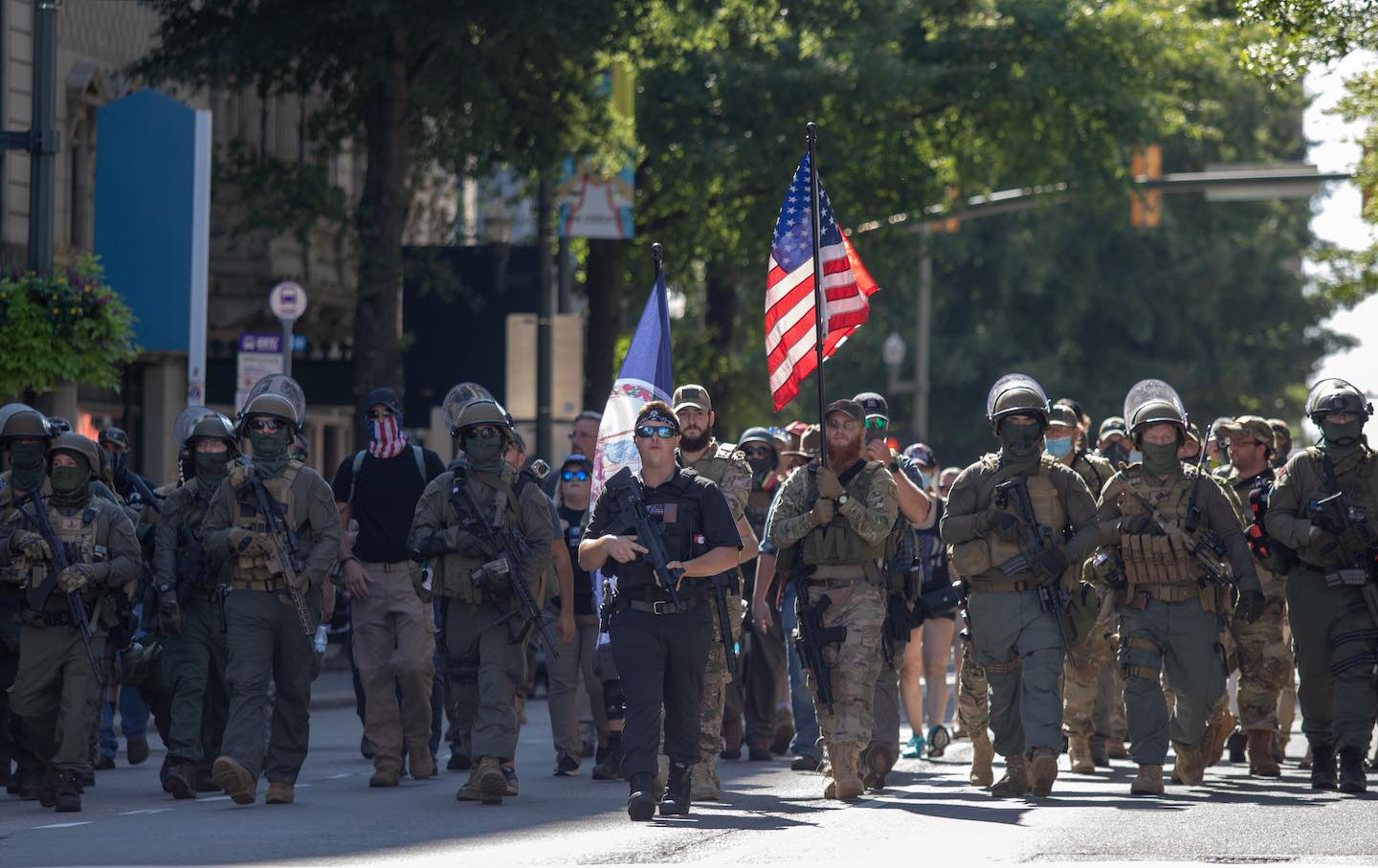 Armed gun rights protesters march down Broad Street.