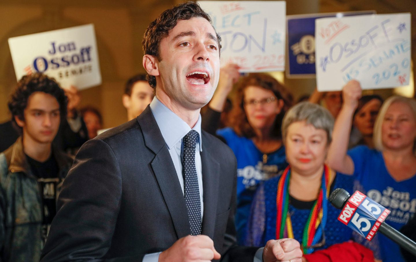 Jon Ossoff speaks to the media, surrounded by a supportive crowd.