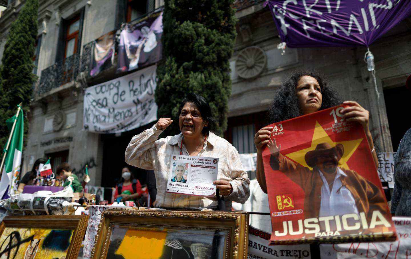 Women stand holding posters and calling for justice.