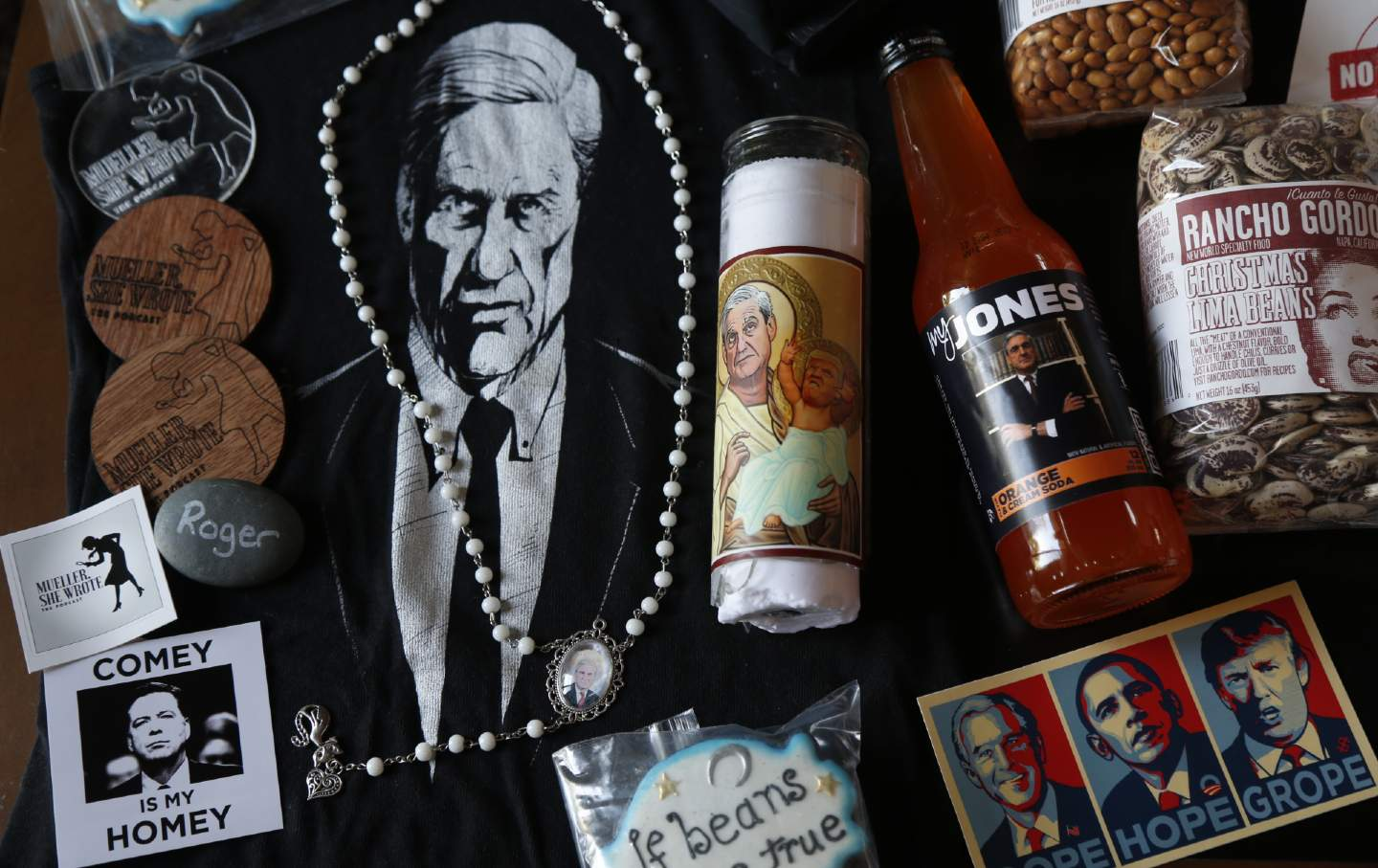 A collection of gift items with Robert Mueller's face on them, including a necklace, a candle, and a poster.