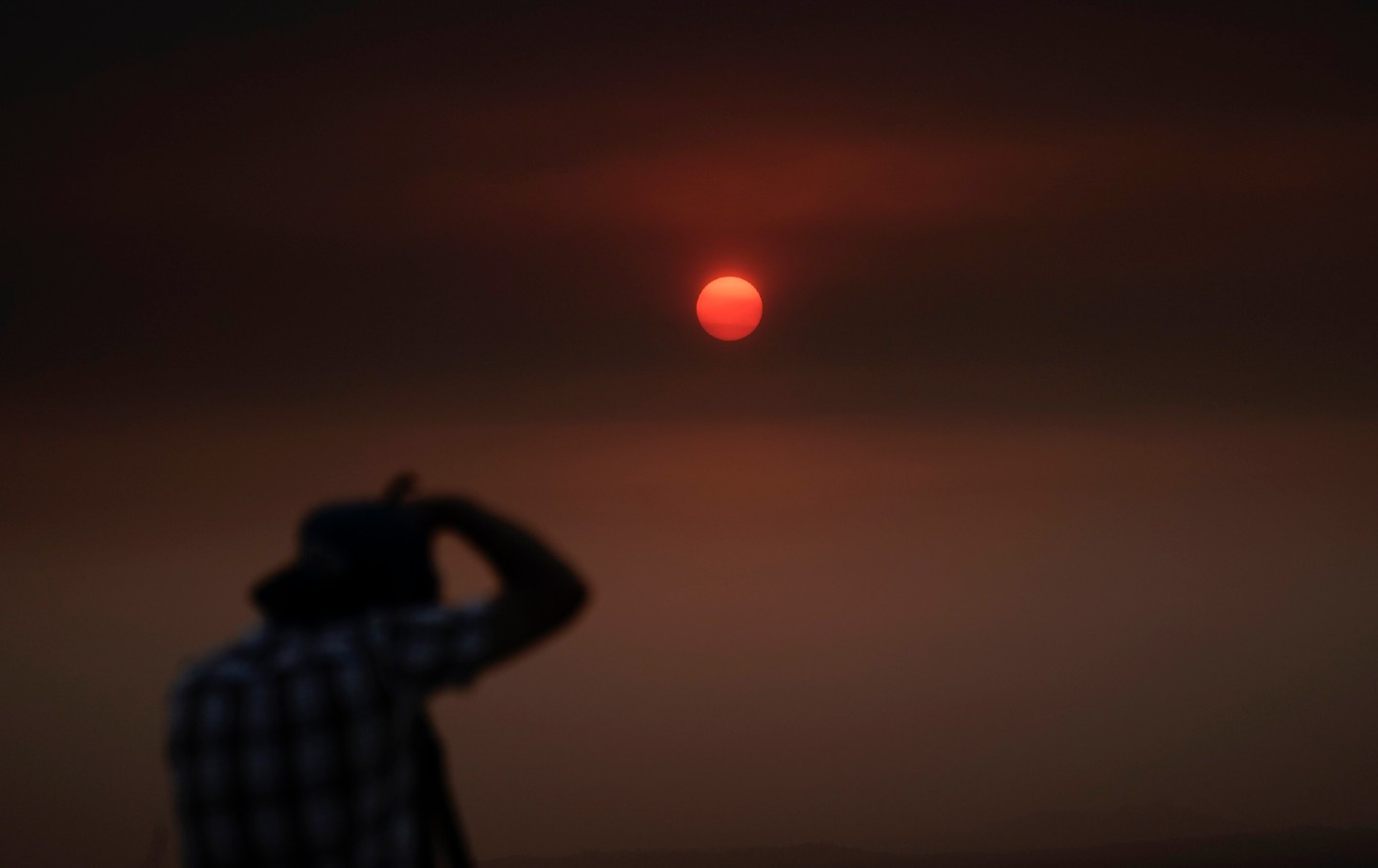 A man takes a photo of the sun in a blood orange sky during the West Coast fires