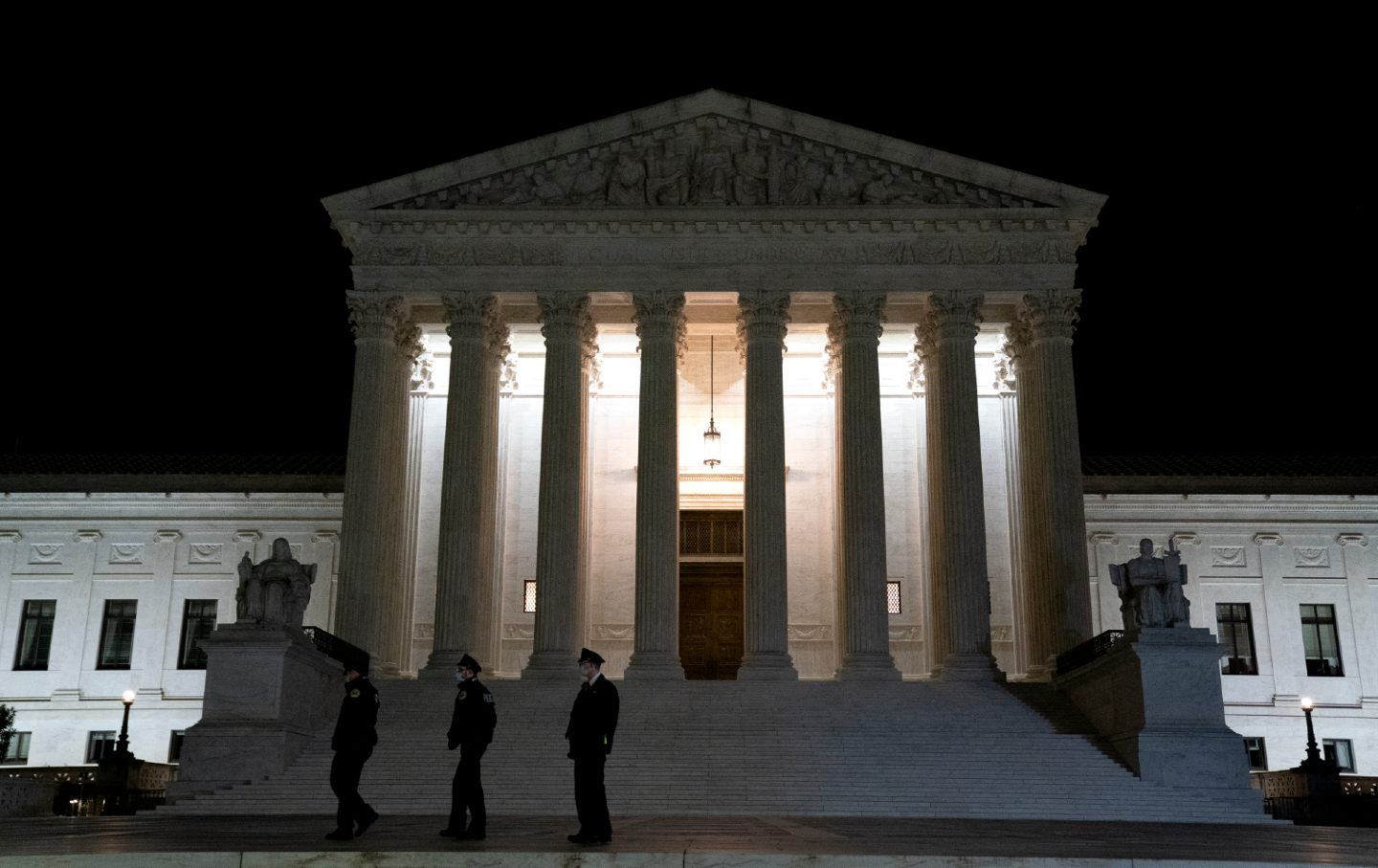 Three police officers stand outside the Supreme Court building at night