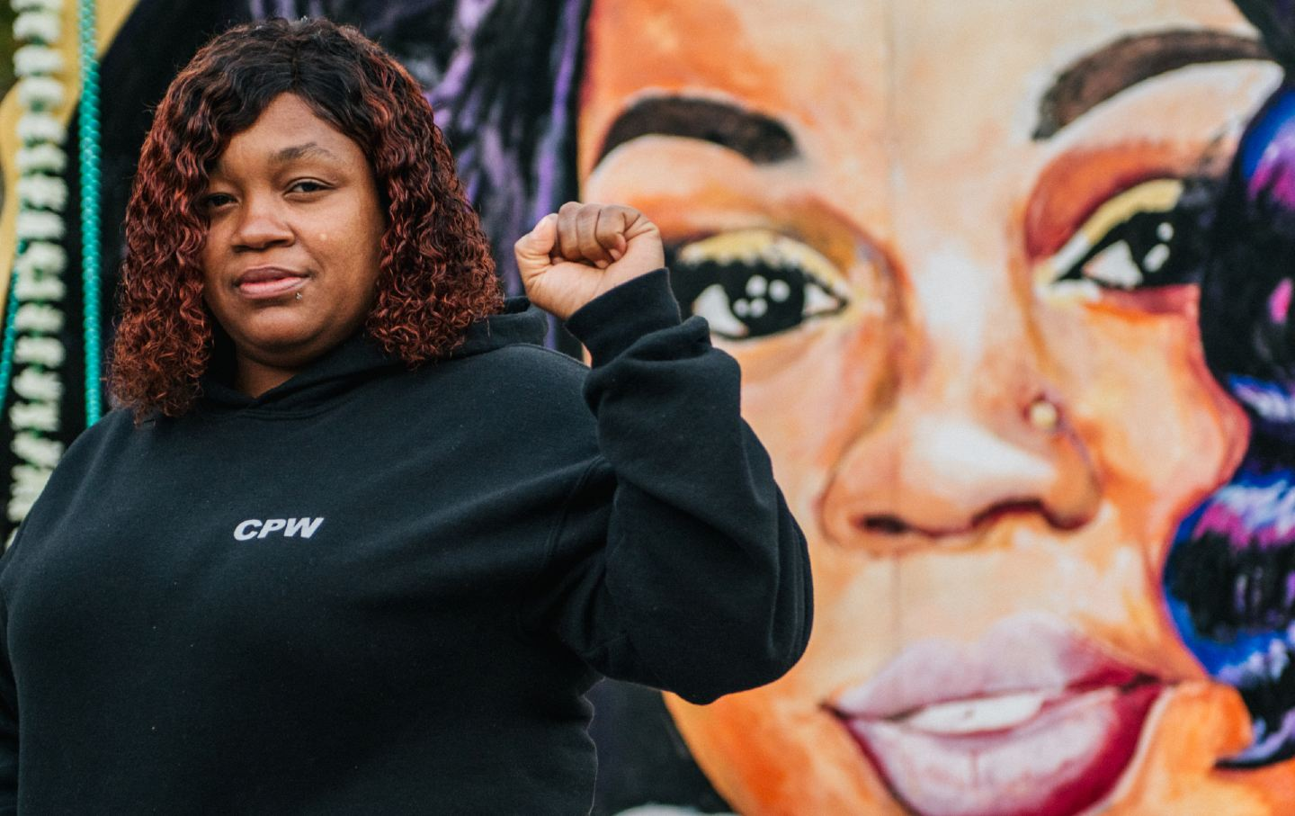 Tamika Palmer holds her first up in front of a mural of Breonna Taylor's face