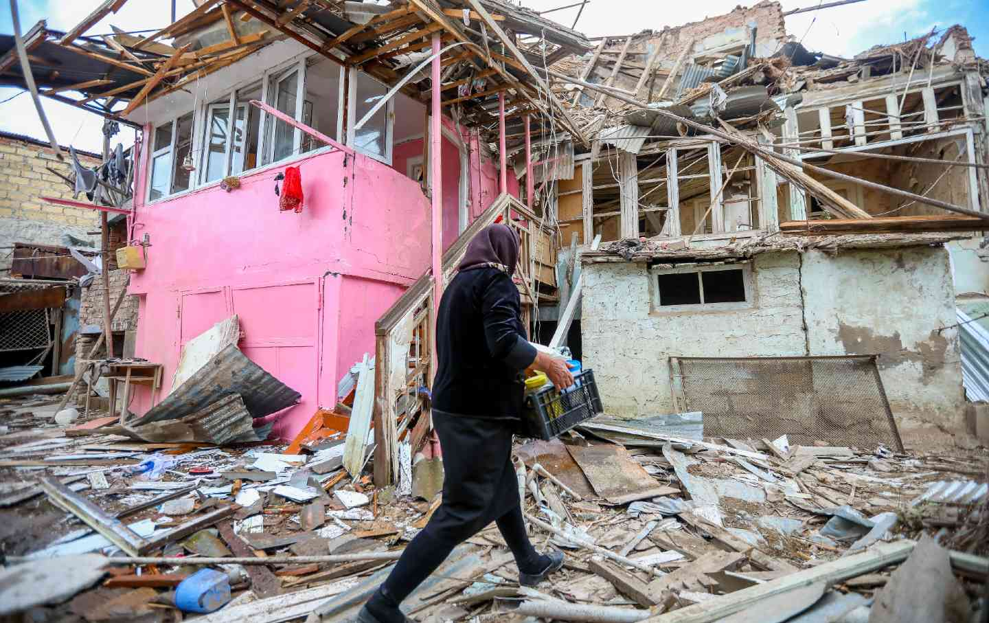 A woman walks past a severely damaged house surrounded by debris