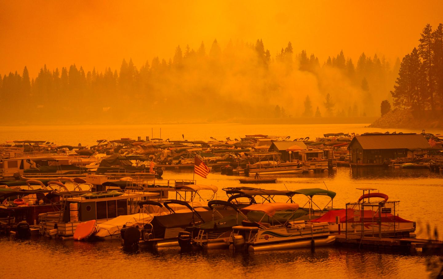 The sky is orange and smoky above the lake, where several boats are docked.