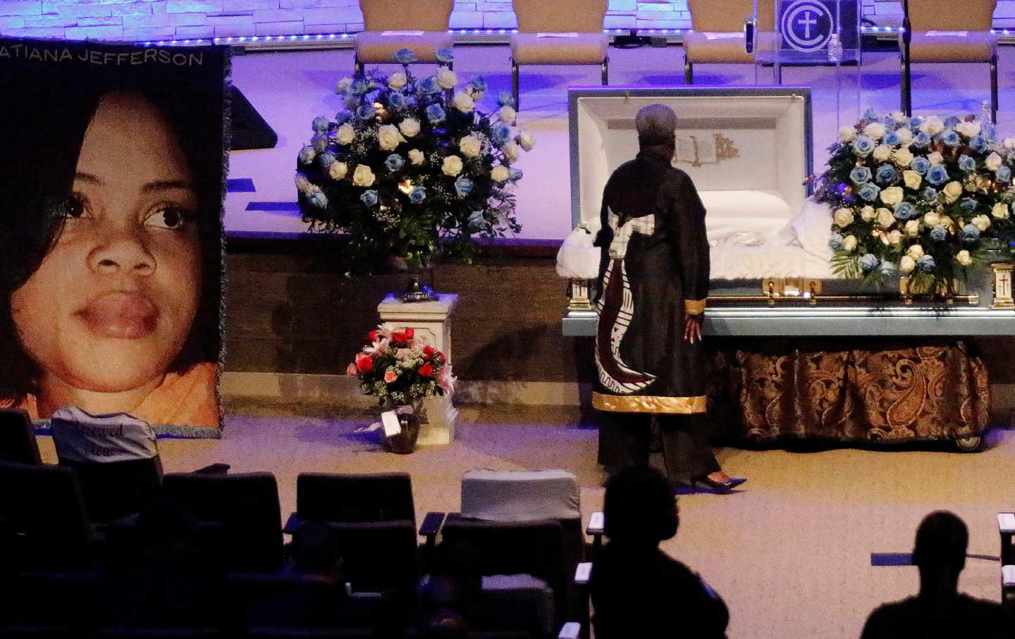 A woman dressed in black stands over Atatiana Jefferson's casket, while others wait behind her. A large photo of Jefferson is displayed to the left of the casket