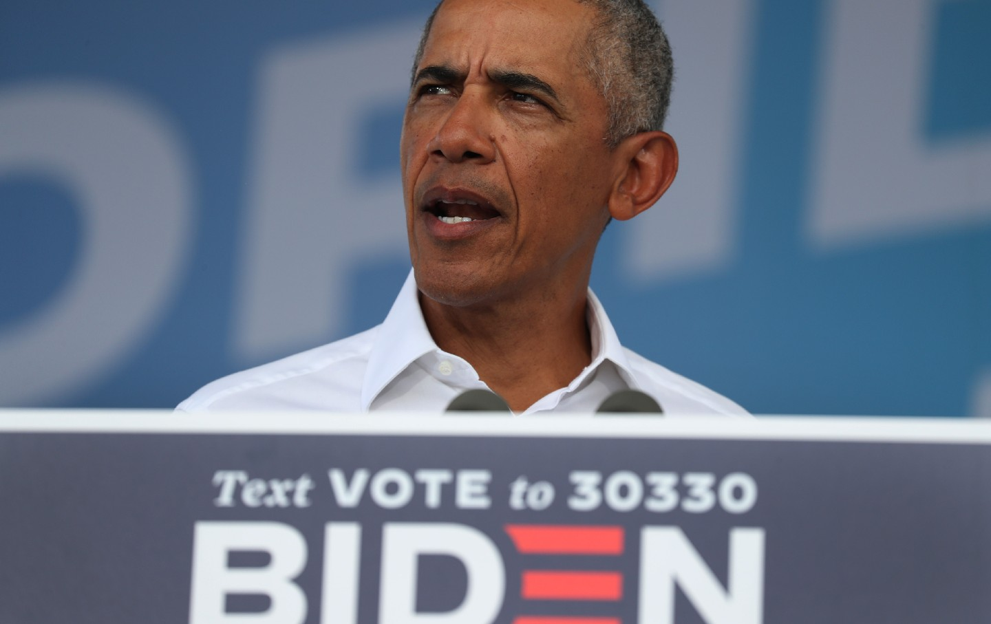 Barack Obama speaks to a crowd in front of a Biden 2020 sign