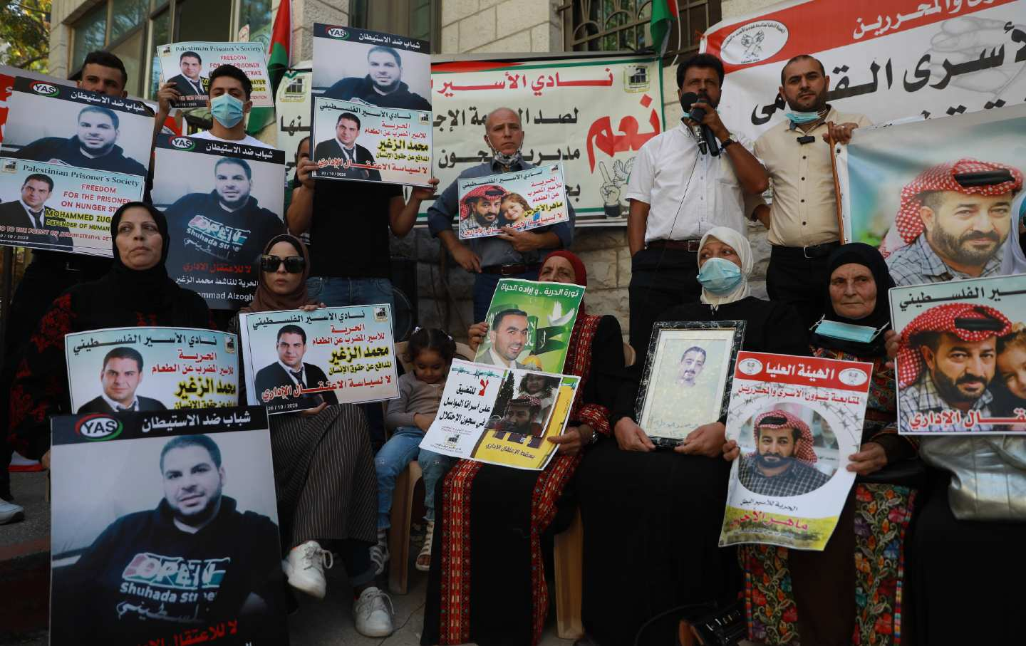 A crowd of people sit and stand holding posters, some bearing the picture of Maher al-Akhras.