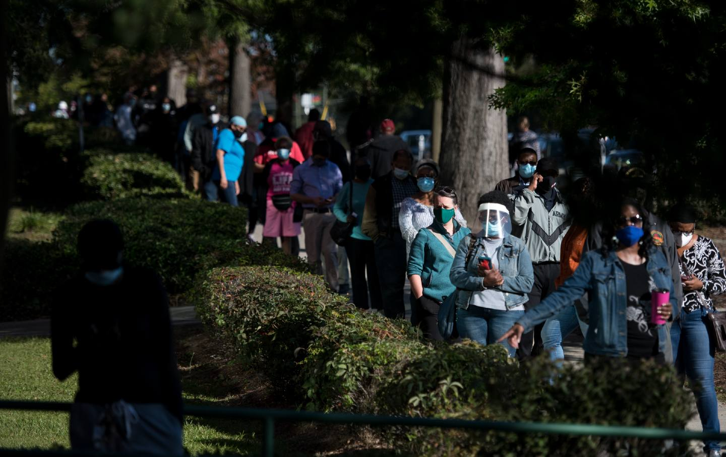 People wearing masks and face shields wait in a long line for early voting