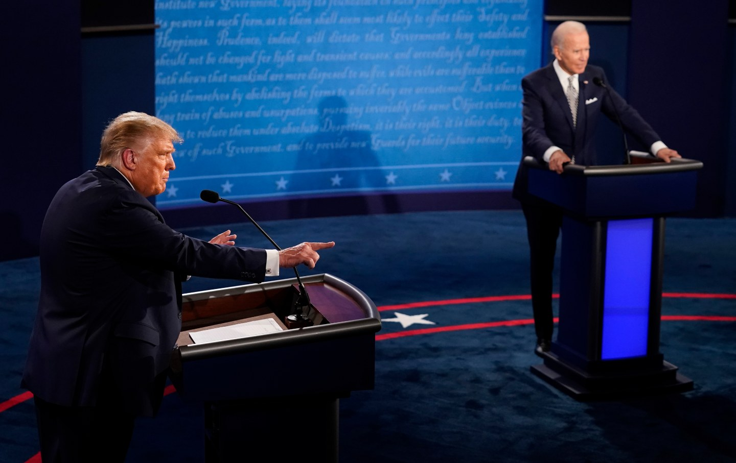 Donald Trump pointing with Joe Biden in the background