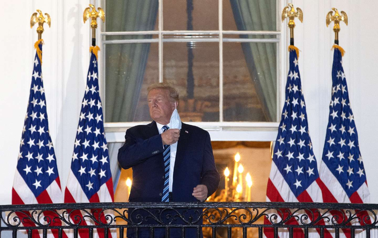 Donald Trump stands on the balcony of the White House taking off a surgical mask