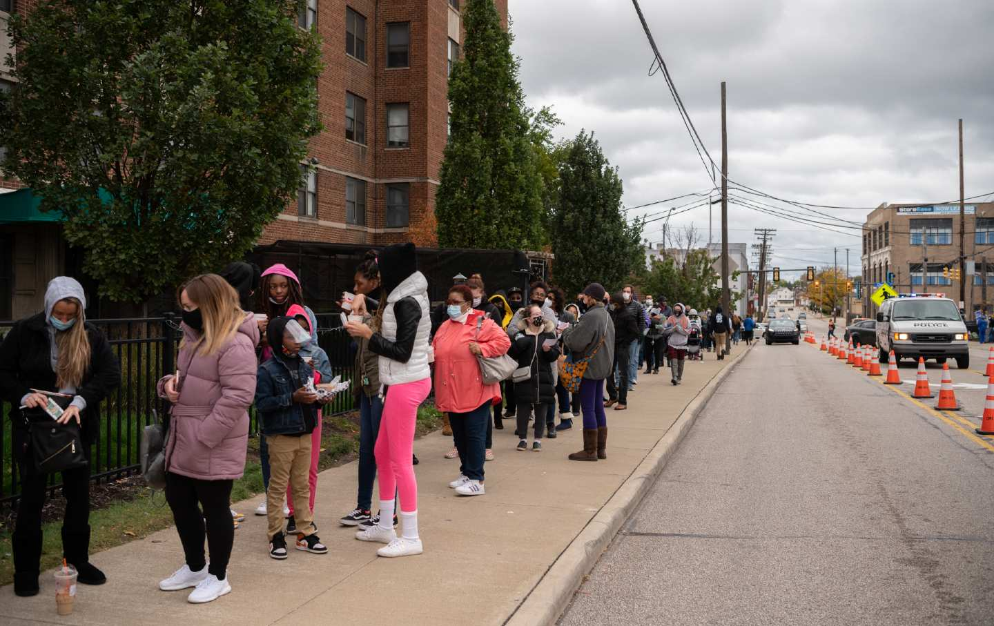A line of voters stretches across a block on the left, while cars are seen driving down a road on the right.