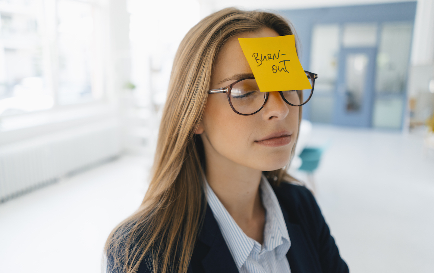 Young businesswman with yellow sticky note on her forehead