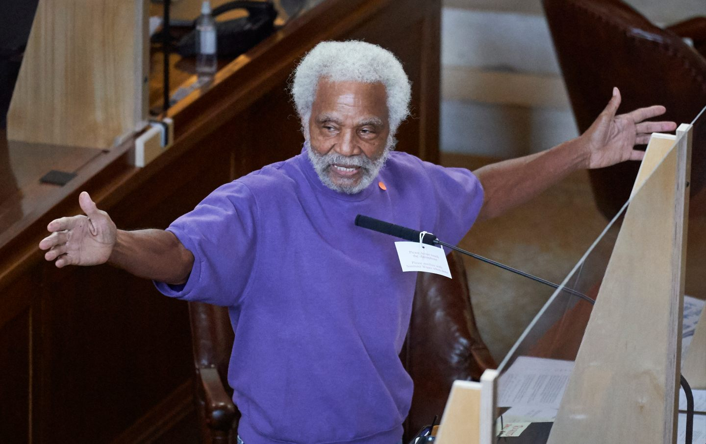Ernie Chambers extends his hands while speaking in front of a microphone