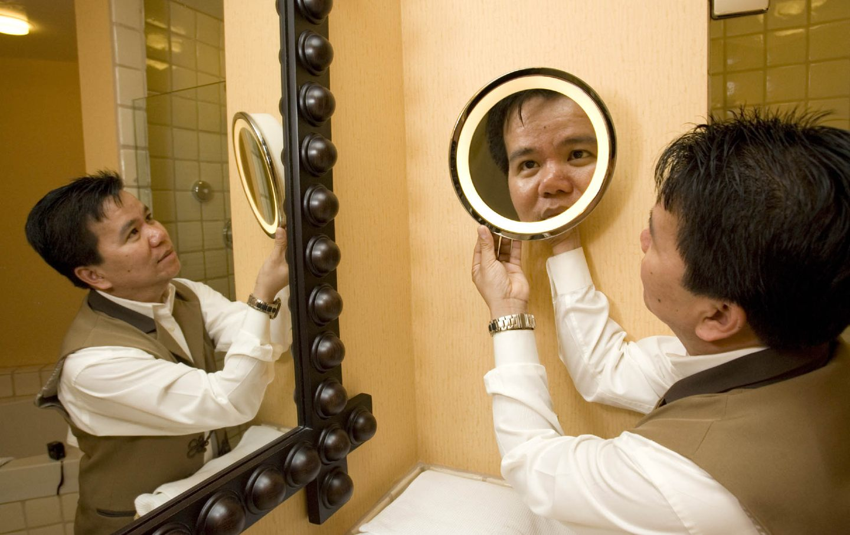 A man in a housekeeping uniform adjusts a mirror in a bathroom.