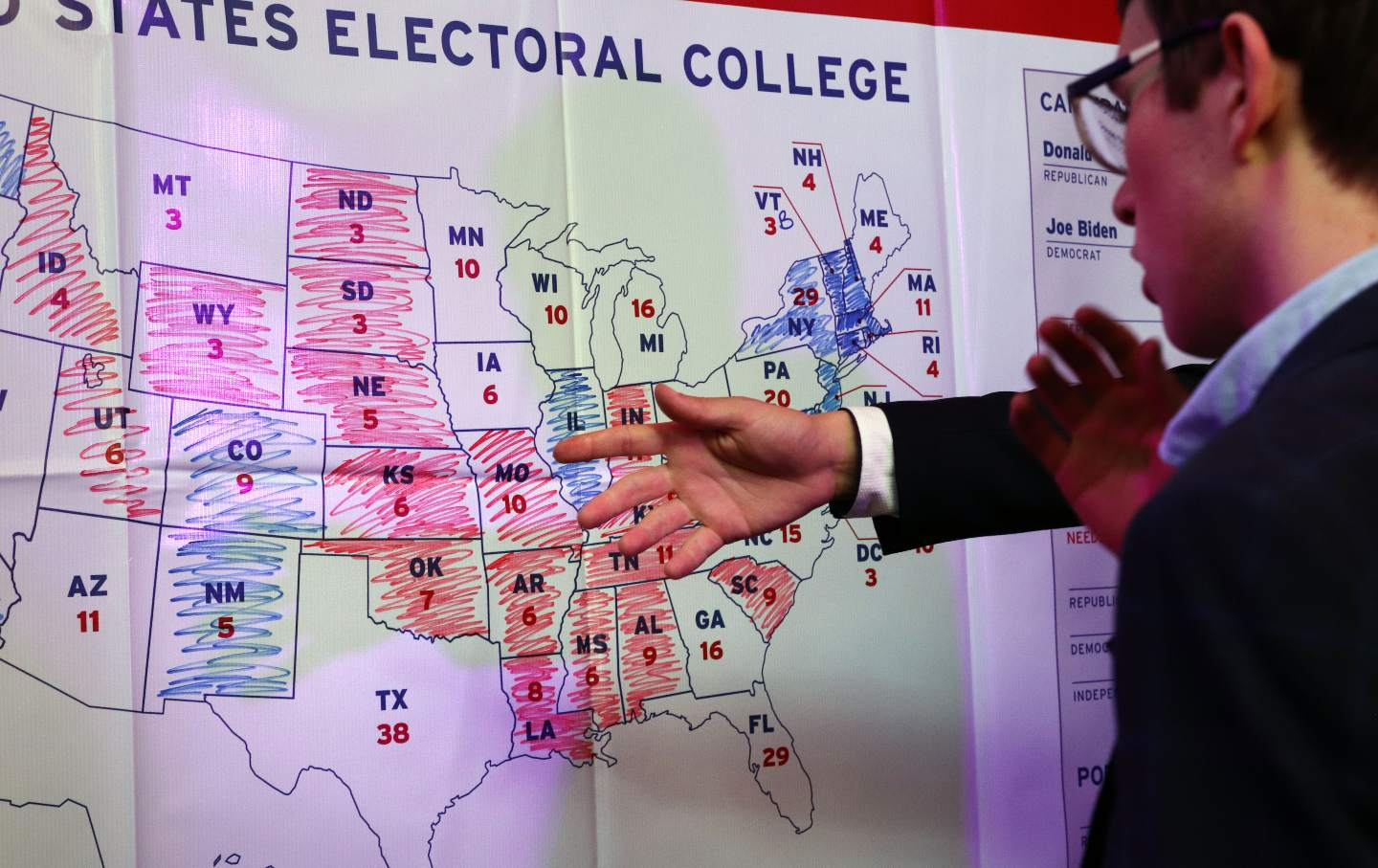 Young man looks at electoral map colored in with markers