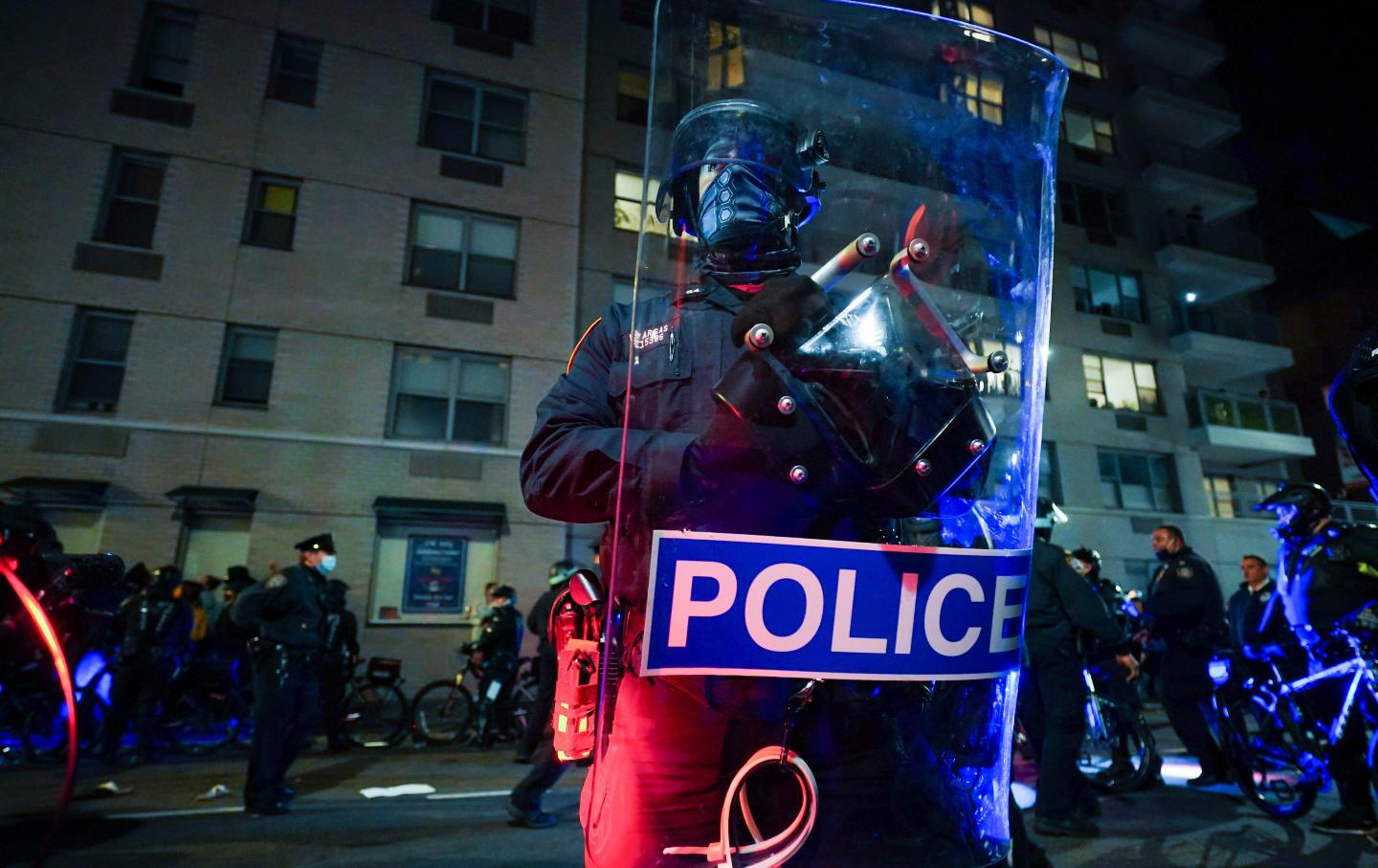 A police officer holds a riot shield that reads POLICE