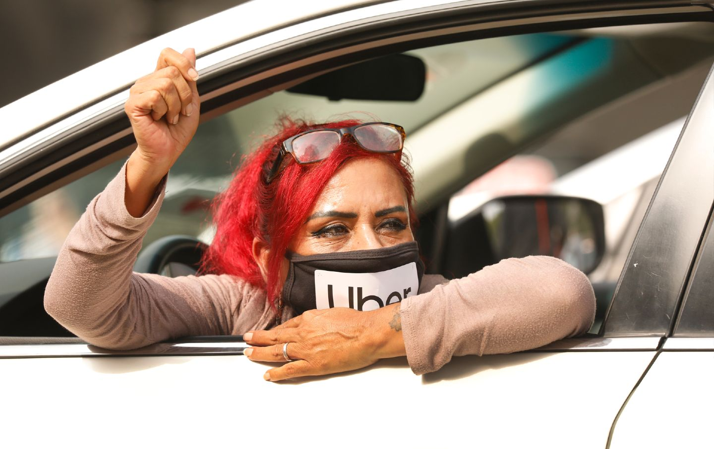 A woman with pink hair wearing a mask that says