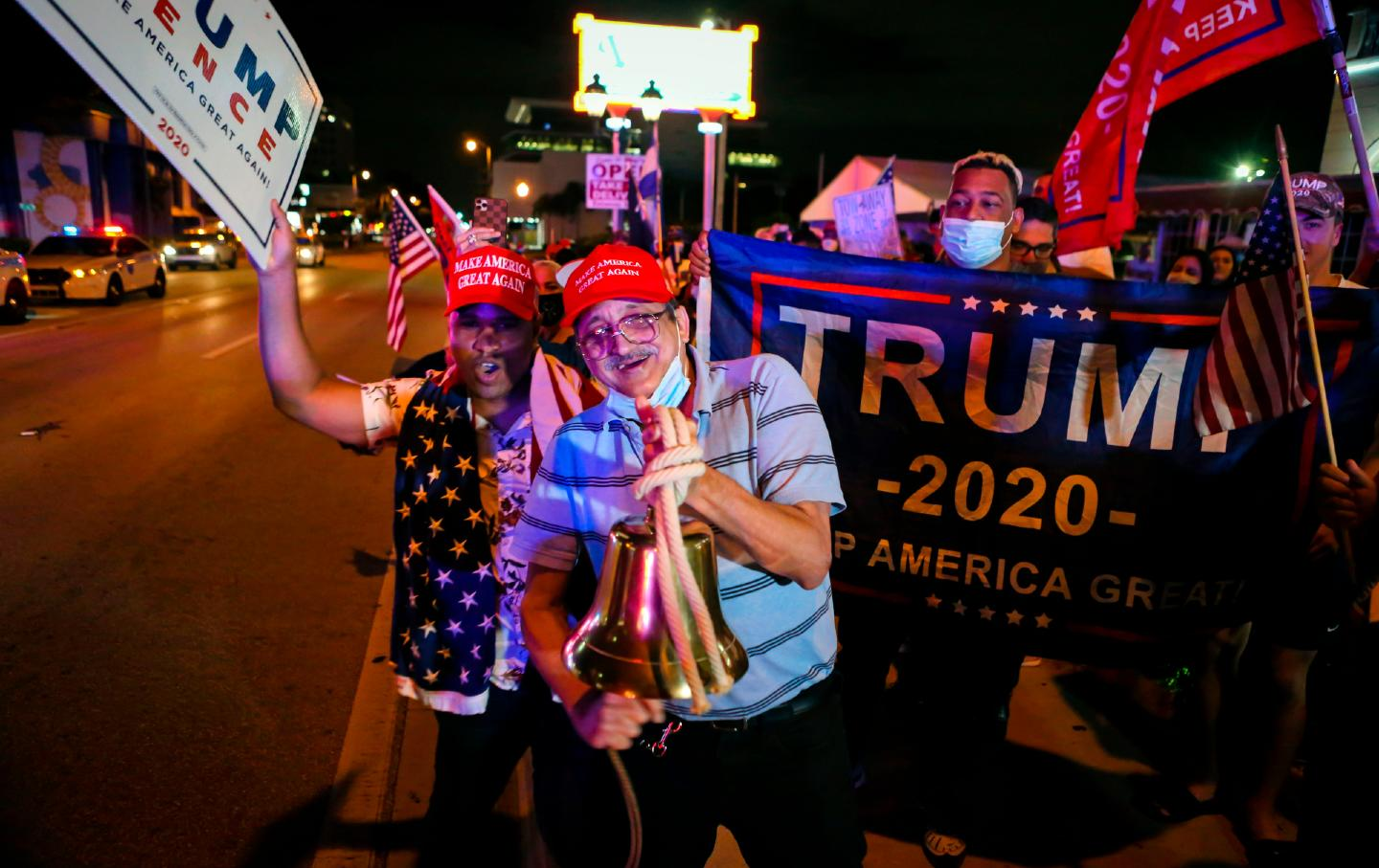 Two supporters in red MAGA hats pose for the camera, behind them is a supporter holding a Trump 2020 sign.