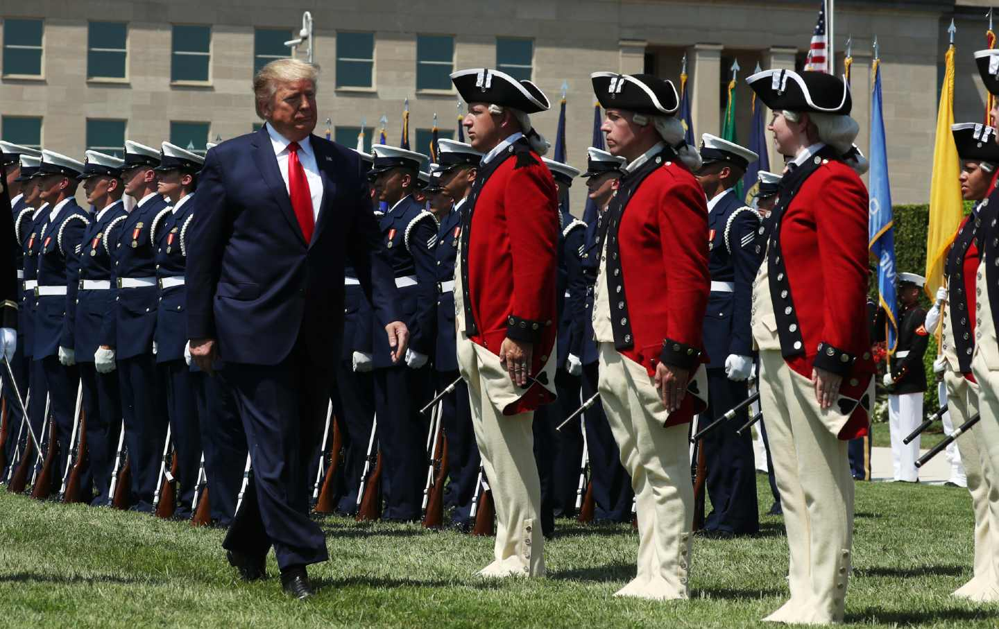Donald Trump walks past a row of troops in full uniform.