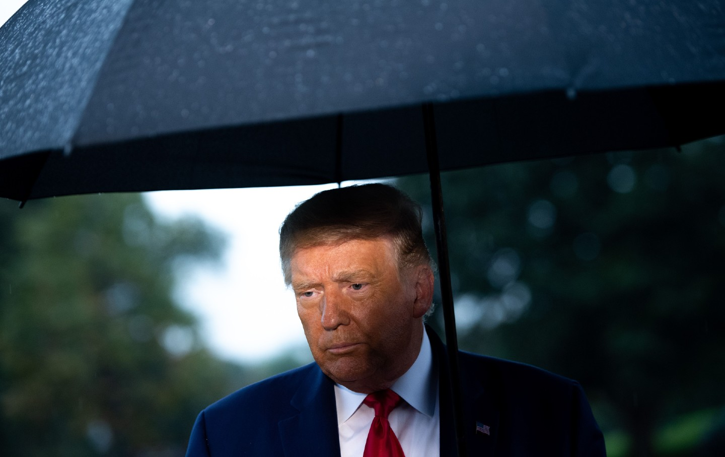 Donald Trump stands looking forlorn in the rain under a black umbrella